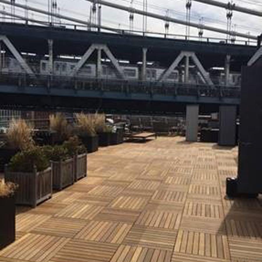 Vista do terraço do prédio com piso de madeira na parte inferior.