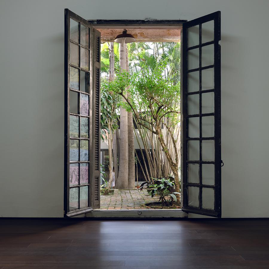 Sala vazia com portas abertas para um jardim no exterior, com iluminação natural.