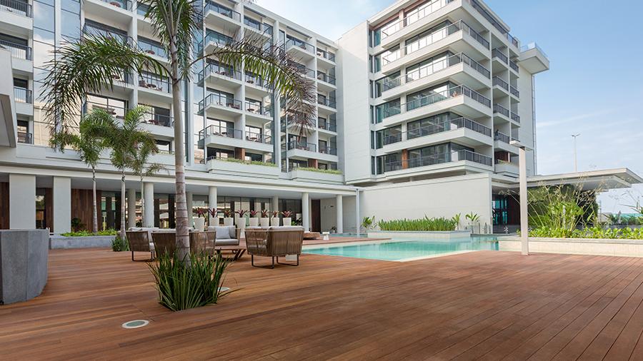 Piso de madeira em deck com piscina, palmeiras e cadeiras espalhadas. Ao fundo, um edifício com grandes janelas de vidro.