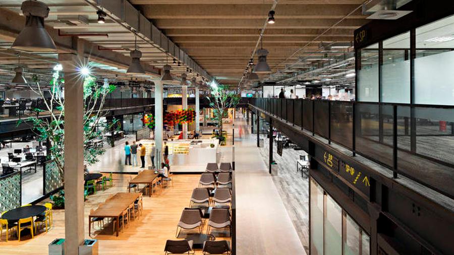 Salão do Mercado Livre com mesas e cadeiras dispostas sob piso de madeira Indusparquet.