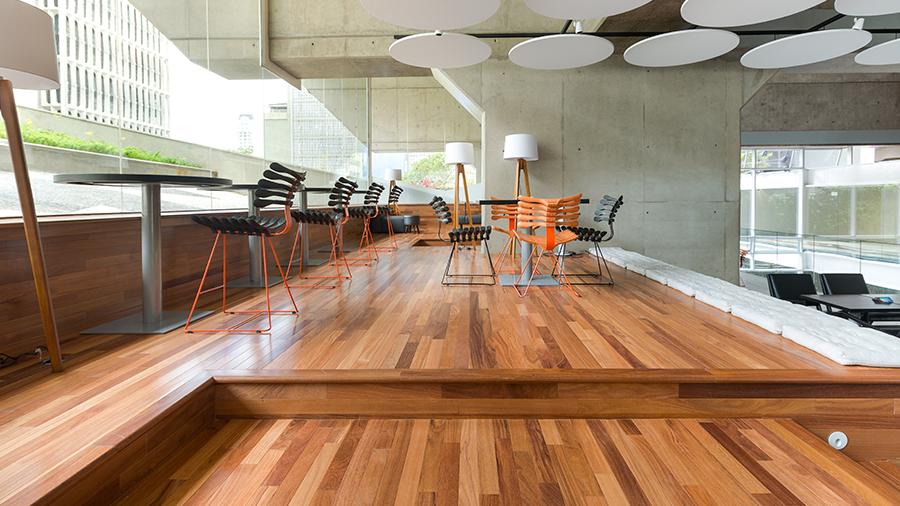 Área interna de edifício com mesas e cadeiras espalhadas sobre piso de madeira, à esquerda janelas de vidro com vista para área externa