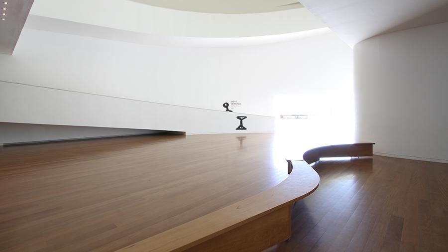 Salão iluminado por luz natural com piso de madeira e paredes brancas