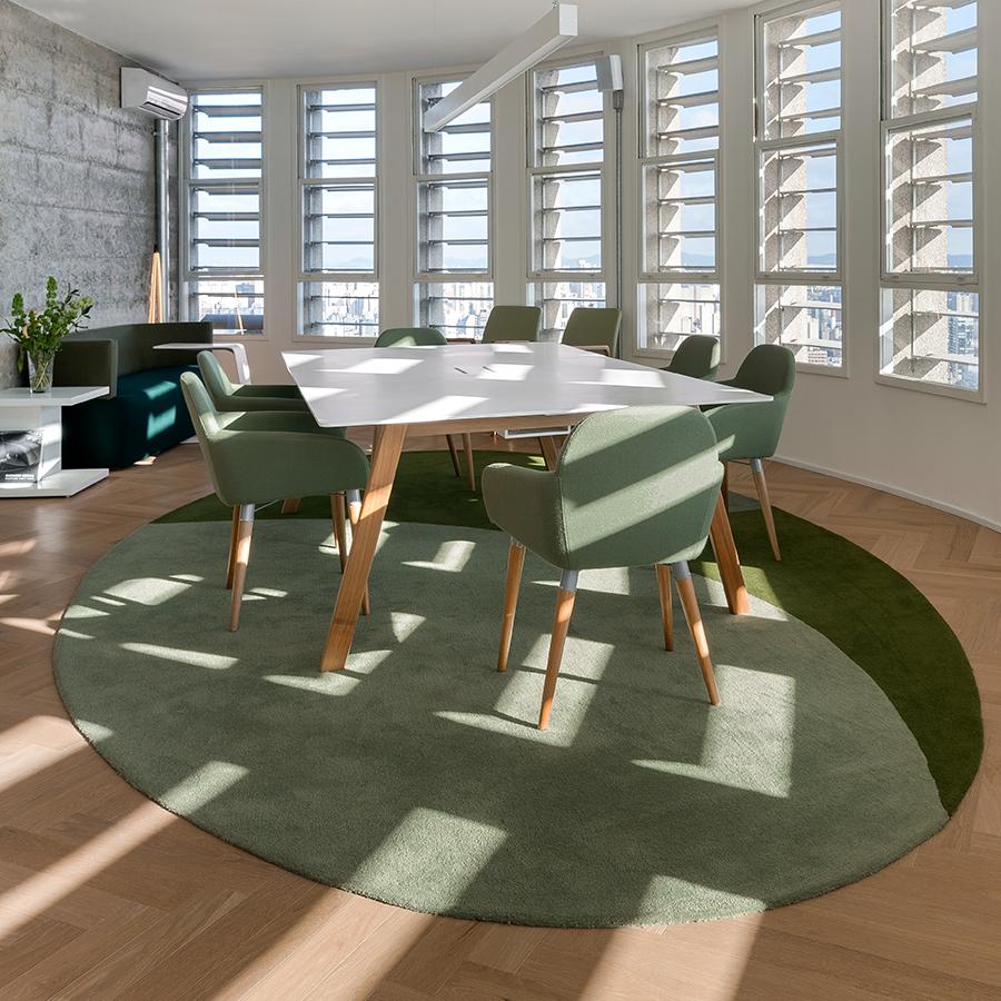 Escritório iluminado por luz natural de janelas abertas. Ao centro, mesa com cadeiras ao redor, disposta sob tapete redondo e piso de madeira.