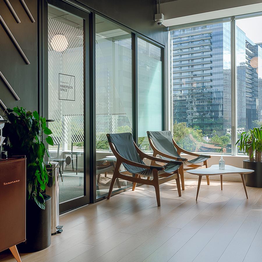Espaço de trabalho com cadeiras e grandes janelas de vidro.