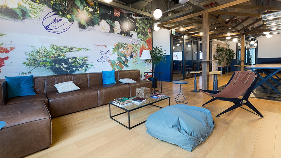 Ambiente com piso de madeira e papel de parede colorido. À esquerda, sofá com almofadas e mesinha de centro à frente. Mesas, cadeiras e pufe à direita. Ao fundo, estrutura de madeira com luminárias suspensas.