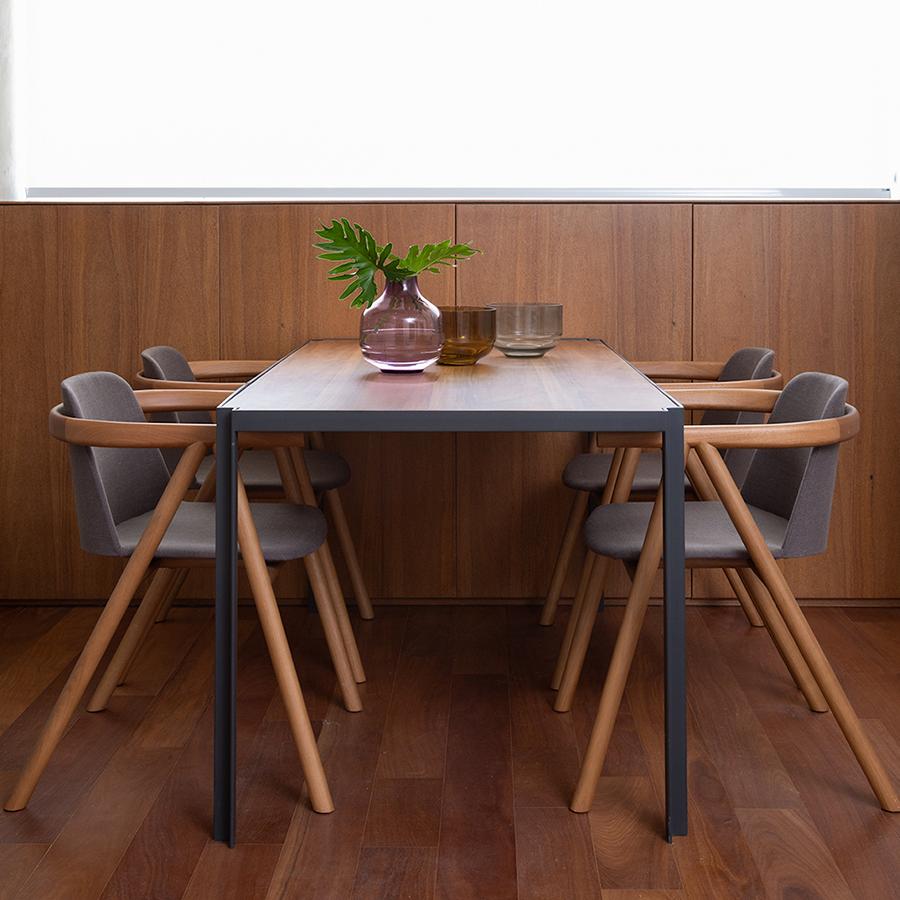 Mesa de jantar rodeada de cadeiras, com vasos de vidro em cima. Piso e parede revestidos em padeira.