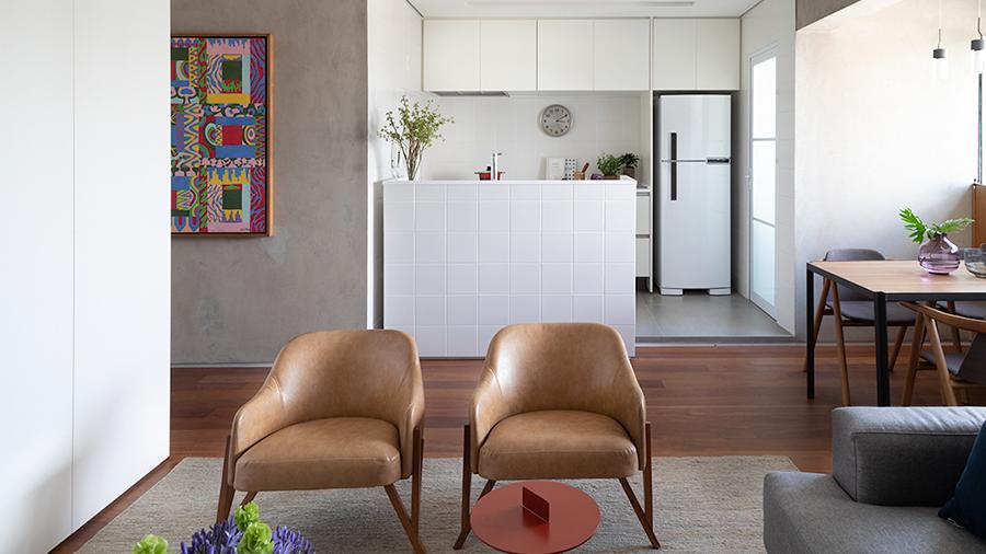 Sala de estar com duas poltronas e sofá à direita. Ao fundo, cozinha com grande bancada e armários suspensos, à direita espaço com mesa de jantar.