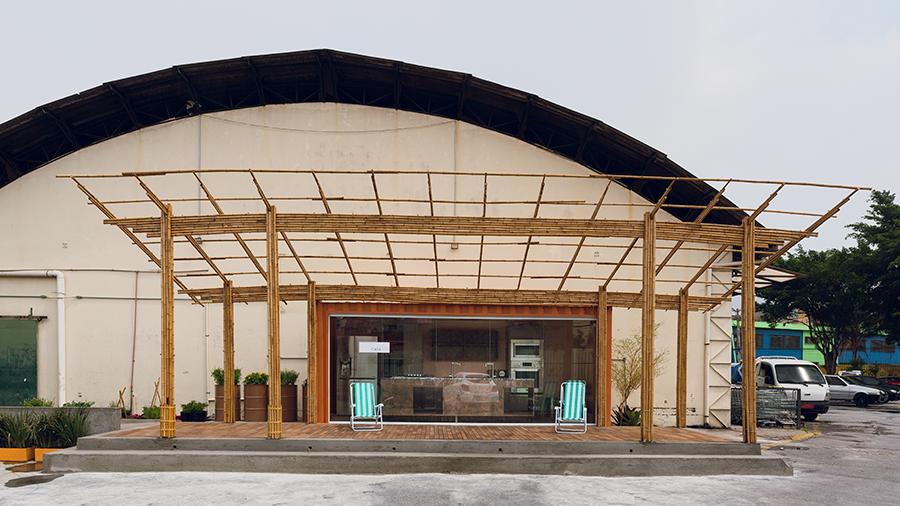 Contêiner com estrutura de bambu e piso de madeira situado em um grande estacionamento.