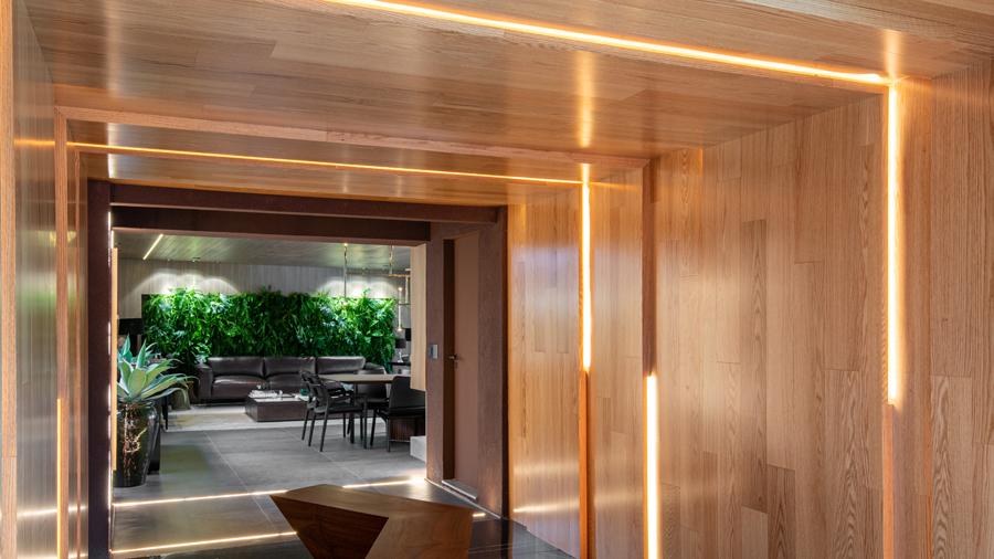 Sala com revestimento de madeira, mesa de jantar rodeada de cadeiras. Ao fundo painel com quadros, plantas e televisão.
